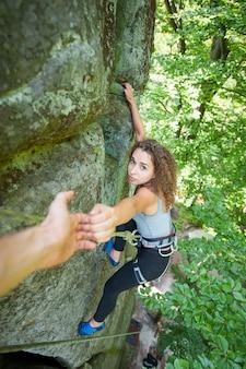 Wspinacz pomaga kobiecej wspinaczce, aby osiągnąć szczyt góry