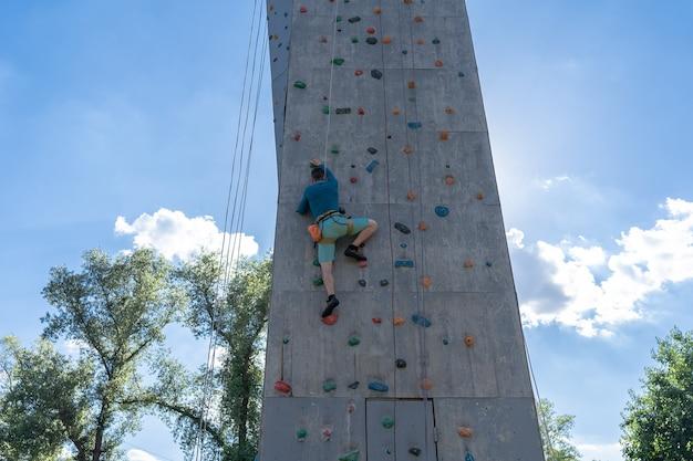 Wspinacz sportowca trenujący na świeżym powietrzu z błękitnym niebem, wspinający się po sztucznej kolorowej ścianie skalnej