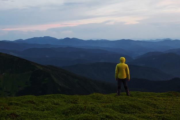 Wspinacz stoi na wzgórzu. majestatyczne karpaty. piękny krajobraz. widok zapierający dech w piersiach.