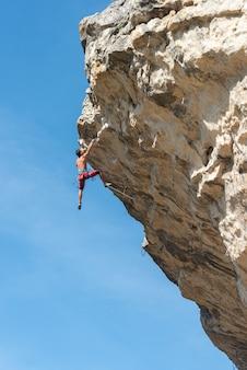 Wspinacz wiszący na rękach na szczycie szczytu