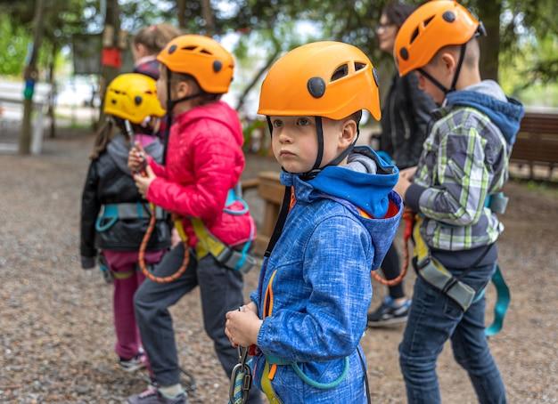 Wspinaczka przygodowa park linowy - dzieci na kursie w kasku górskim i sprzęcie ochronnym.
