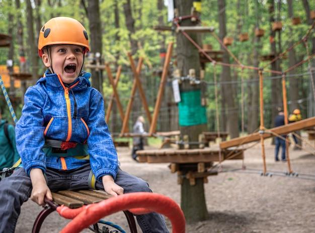 Wspinaczka przygodowa w parku linowym - mały chłopiec na kursie w kasku i sprzęcie ochronnym.