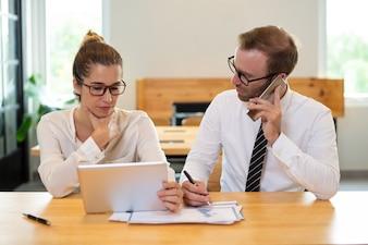 Współpracownicy biznesowi pracujący i używający przyrząd.