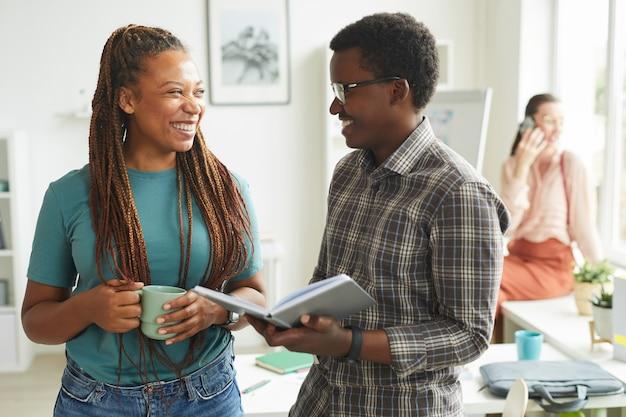 Współczesna african-american kobieta rozmawia z kolegą i uśmiecha się radośnie, stojąc w biurze