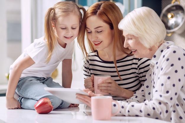 Współczesna cyfryzacja. śliczna mała dziewczynka siedzi na blacie w kuchni i ogląda wideo na laptopie wraz z matką i babcią pijąc kawę