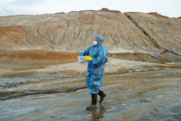 Współczesna kobieta-naukowiec w osłonach ochronnych, respiratorze, gumowych rękawiczkach i butach z plastikowym pojemnikiem na wzgórzach i na niebie