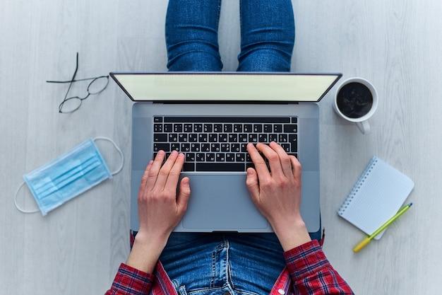 Współczesna kobieta pracuje w domu przy komputerze online podczas kwarantanny i izolacji w momencie wybuchu koronawirusa