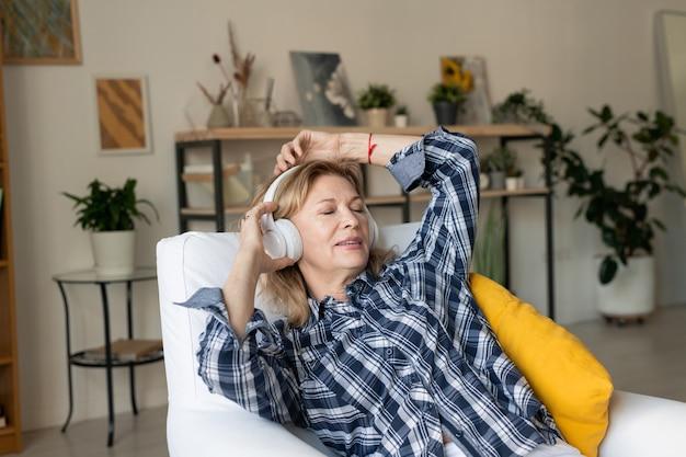 Współczesna kobieta w średnim wieku ze słuchawkami, słuchająca relaksującej muzyki, leżąc na poduszkach w fotelu w salonie