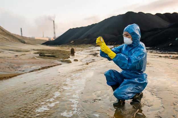 Współczesna młoda ekolożka lub badaczka odzieży ochronnej i respiratora umieszczająca próbkę gleby w kolbie w obszarze toksycznym