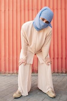 Współczesna młoda islamska kobieta w hidżabie i swobodnym stroju, patrząc na ciebie kucając nad czerwoną ścianą