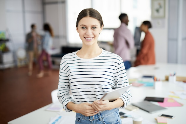 Współczesna młoda kobieta pozuje w biurze