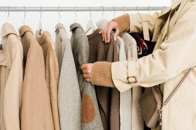 Współczesna młoda kobieta w beżowym prochowcu i swetrze z dzianiny wybiera casualowe ubrania z nowej sezonowej kolekcji w butiku