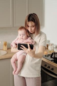 Współczesna młoda kobieta ze smartfonem i dzieckiem komunikującym się na czacie wideo