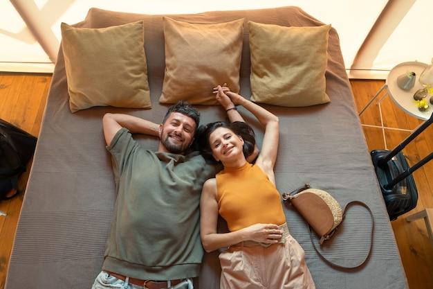 Współczesna młoda para trzymająca się za ręce leżąc na łóżku