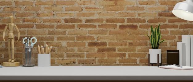 Współczesna przestrzeń do pracy z artykułami papierniczymi, dostawami, dekoracjami i miejscem na kopię na stole z ceglaną ścianą,