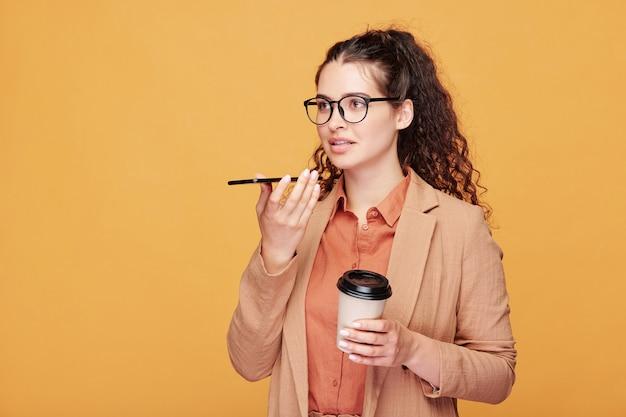 Współczesna studentka po filiżance kawy podczas przerwy między lekcjami i nagrywanie wiadomości głosowej na smartfonie