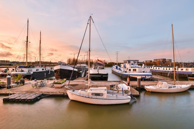 Współczesne jachty i statki pływające w pobliżu molo na wodzie kanału przed zachmurzonym niebem w porcie
