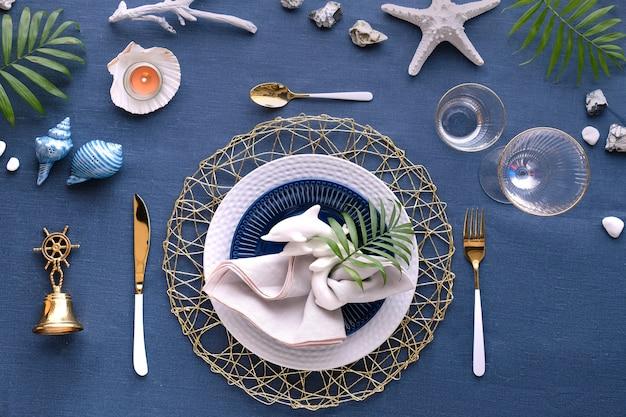 Współczesne nakrycie stołu z dekoracjami morskimi na klasycznym niebieskim lnianym materiale.