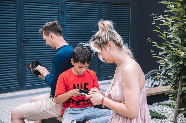 Współczesne pokolenie ludzi korzystających ze smartfonów. rodzina używa smartfonów do chodzenia. miasto w weekend letni dzień. wysokiej jakości zdjęcie. styl życia