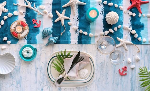 Współczesne ustawienie letniego stołu z morskimi dekoracjami na niebiesko-białym prążkowanym bieżniku