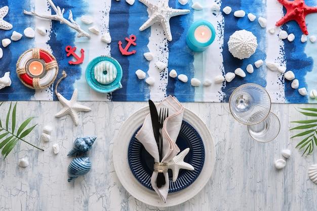 Współczesne ustawienie stołu letniego z morskimi dekoracjami na niebiesko-białym prążkowanym bieżniku