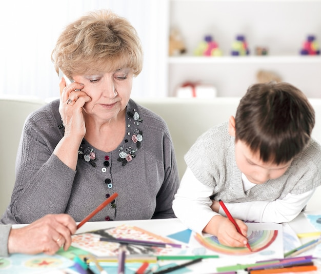 Współcześni dziadkowie odwiedzający wnuka siedzącego przy stole w przedszkolu. koncepcja edukacji