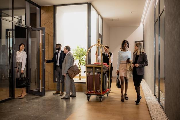 Współcześni ludzie biznesu komunikują się, podczas gdy tragarz porusza się między nimi i pcha wózek z bagażem do hotelu