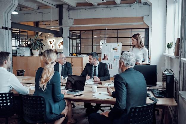 Współcześni specjaliści od marketingu w eleganckich strojach wizytowych omawiają świeże pomysły biznesowe podczas pracy w biurze