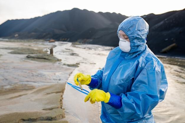 Współczesny badacz lub ekolog wkłada do opakowania butelkę z próbką brudnej wody podczas badania skażonego terenu