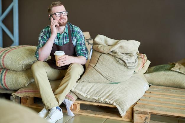 Współczesny barista siedzący na workach z kawą