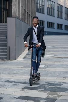 Współczesny biznesmen afroamerykański jeździ skuterem elektrycznym po zakończeniu dnia pracy o godz