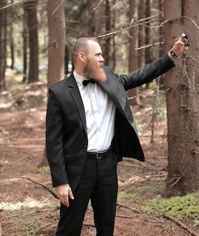Współczesny biznesmen robi selfie w sosnowym lesie