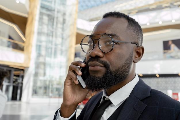 Współczesny biznesmen ze smartfonem na ucho