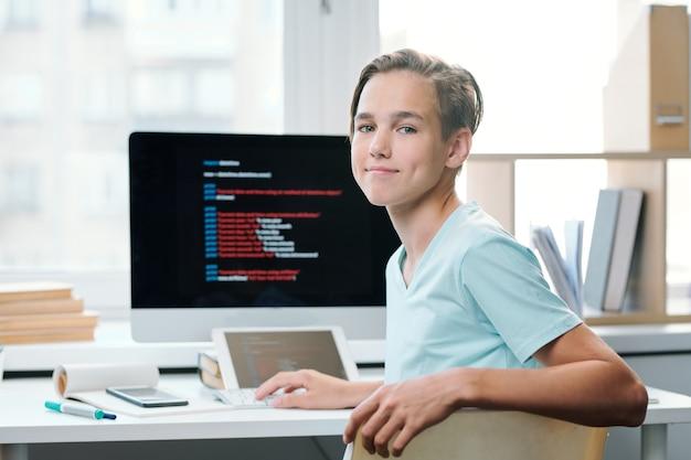 Współczesny chłopiec w casual, patrząc na ciebie, siedząc przy biurku z monitorem komputera przed szkołą