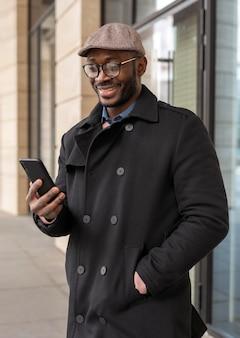 Współczesny człowiek za pomocą swojego telefonu na zewnątrz