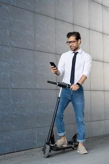 Współczesny dobrze ubrany pracownik mobilny przewijający smartfon podczas poruszania się po ścianie budynku na skuterze