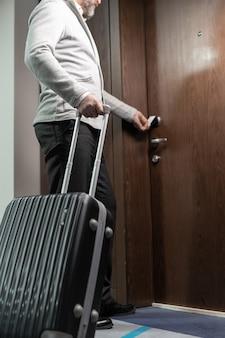 Współczesny dojrzały biznesmen lub podróżnik z bagażem używający karty do otwierania drzwi pokoju hotelowego, którą otrzymał w recepcji