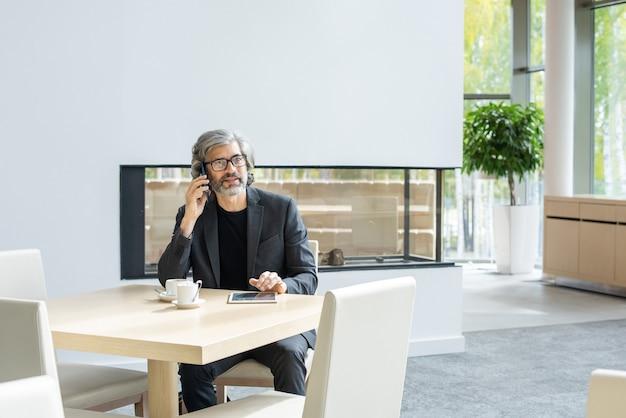 Współczesny dojrzały biznesmen w stroju formalnym, siedzący na kanapie w luksusowej restauracji, rozmawiający na smartfonie i używający touchpada