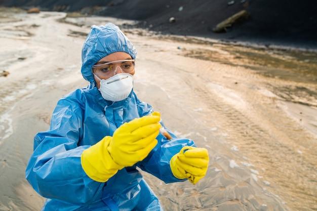 Współczesny ekolog w rękawiczkach, kombinezonach, respiratorze i okularach patrzący na kolbę z próbką brudnej wody lub gleby w zanieczyszczonym obszarze