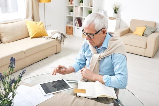 Współczesny emeryt z tabletem cyfrowym i biletami do rezerwacji online kartą bankową, siedząc przy stole w swoim pokoju w domu