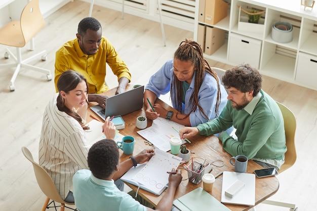 Współczesny kreatywny zespół pracujący razem przy zagraconym stole z kubkami i przedmiotami stacjonarnymi, pracujący zespołowo lub studiujący koncepcję