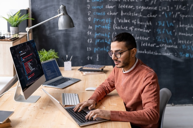 Współczesny menedżer it w okularach siedzi przy stole przed laptopem w biurze i pracuje z zakodowanymi informacjami