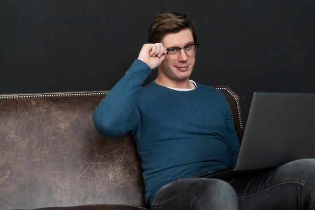 Współczesny mężczyzna sprawdza ogólnospołecznych środki na laptopie