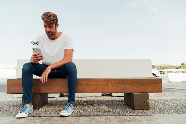 Współczesny mężczyzna wyszukuje telefon na ławce