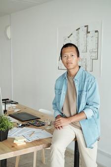 Współczesny młody architekt siedzący na stole przed szkicem na ścianie