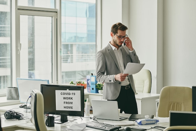 Współczesny młody biznesmen w formalnej odzieży konsultuje klienta przez telefon i przegląda dokumenty w biurze podczas epidemy