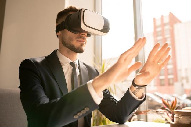 Współczesny młody biznesmen w zestawie słuchawkowym vr dotykając wirtualnego obiektu lub wyświetlacza siedząc w kawiarni przy oknie