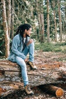 Współczesny młody człowiek siedzący na zwalonym drzewie na ziemi w środku lasu