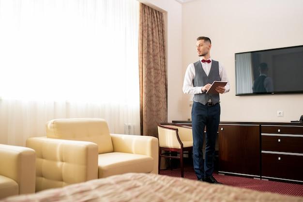 Współczesny młody, elegancki portier stojący w jednym z pokoi hotelowych, patrząc na biały skórzany fotel i wprowadzający informacje na touchpadzie