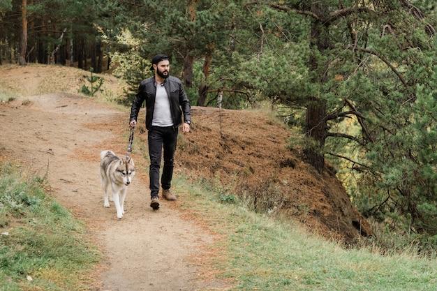 Współczesny młody mężczyzna w codziennym stroju idący chodnikiem, trzymając smycz swojego rasowego psa